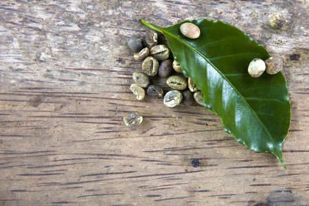 Kopi Luwak coffee beans and leaf on the wooden table Stock Photo