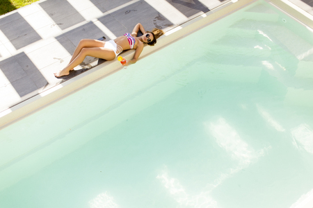 Pretty young woman with drink on the poolside at hot summer day