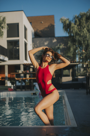 Young woman in red bikini posing by the pool  at hot summer day 免版税图像