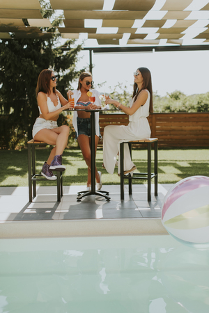 Pretty young women drinking coctail and having fun by the swimming pool at hot summer day