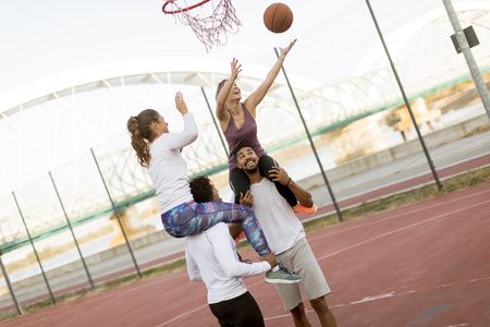 Young women sitting on the men shoulders and holding a basketball at outdoor court on a sunny day