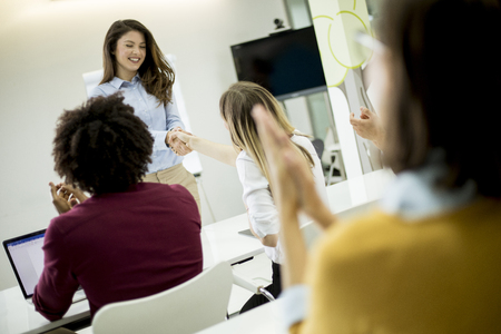 Smiling young woman standing near whiteboard and shaking hand to her female colleague in the small startup office