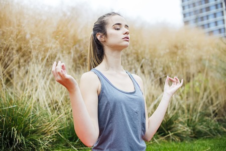 Pretty young woman practices yoga and meditates in the lotus position in the park Stock fotó - 123416455
