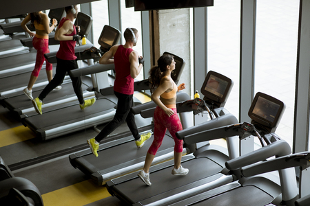 Man and woman doing cardio workout on treadmills in fitness club