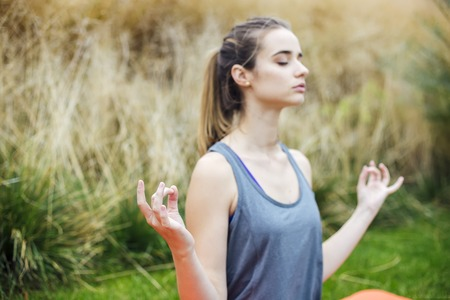 Pretty young woman practices yoga and meditates in the lotus position in the park Stock fotó