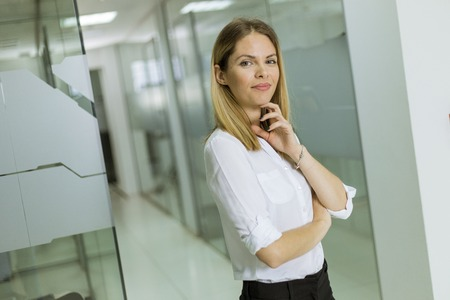 Relaxed pretty confident young businesswoman standing standing in the modern office 版權商用圖片