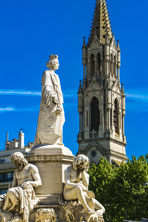 Detail of Pradier fountain at Esplanade Charles-de-Gaulle with Eglise Sainte Perpetue in the background in Nimes, France Stock Photo