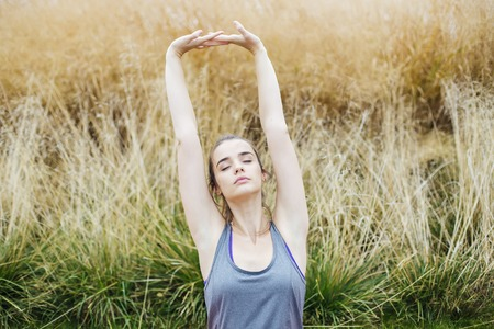 Young woman to practice stretching after yoga on mat outdoor at summer Stock fotó