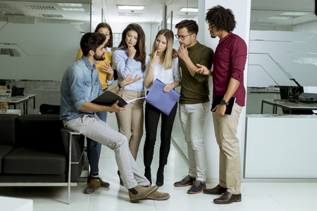 Multiethnic group of young people standing in modern office and brainstorming