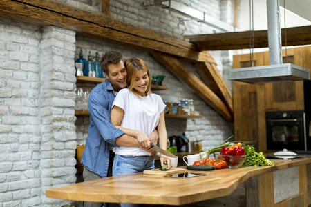 Lovely cheerful young couple cooking dinner together and having fun at rustic kitchen