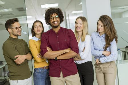 Retrato de grupo de jóvenes empresarios emocionados de pie en la oficina