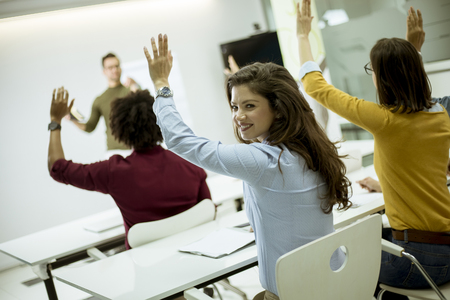Group of young students rising hands to answer the question during the workshop training 写真素材