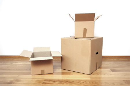 Open cardboard boxes on the floor in empty room, ready for transport Stock Photo