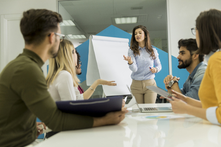 Confident young team leader giving a presentation to a group of young colleagues as they sit grouped by the flip chart in the small startup office