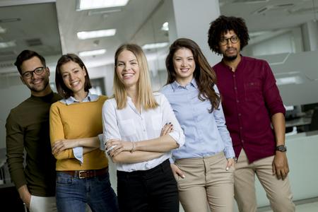 Porträt einer Gruppe junger aufgeregter Geschäftsleute, die im Büro stehen