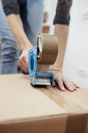 Closeup of the mans hands using a tape dispenser to seal a shipping box