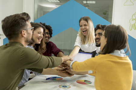 Team of young people stacking hands together over table engaged in teambuilding Stockfoto