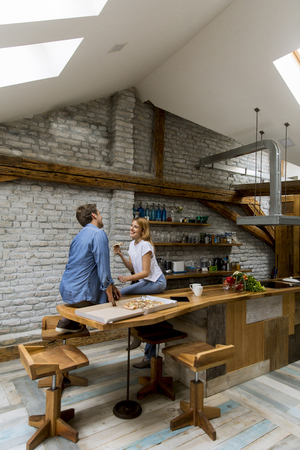 Young couple in love eating pizza for sneck in the rustic home 版權商用圖片