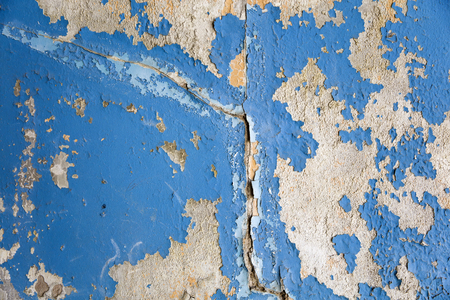 Old wall with the blue colored whitewash falling off fragment with cracks as a background texture Imagens