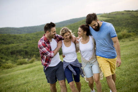 Group of happy young people walking in the summer field