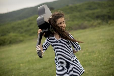 Beautiful young girl carrying her guitar in green nature