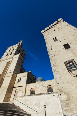 Avignon cathedral (Cathedral of Our Lady of Doms) next to Papal palace (Palais des Papes) under blue sky in Avignon, France