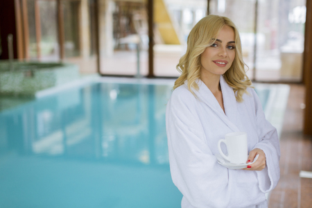 Beautiful young blonde woman in bathrobe relaxing at indoor swimming pool Stock Photo