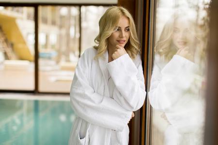 Beautiful young blonde woman in bathrobe relaxing at indoor swimming pool 版權商用圖片