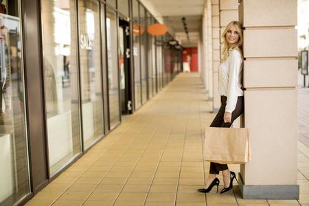 Schöne Frau mit Papiereinkaufstasche, die am Laden steht