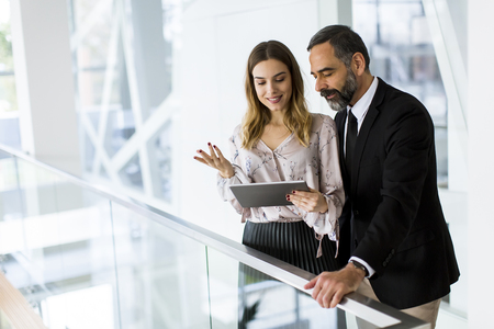 Handsome smiling mature businessman and his cute young female coworker with digital tablet in the modern office Stock Photo