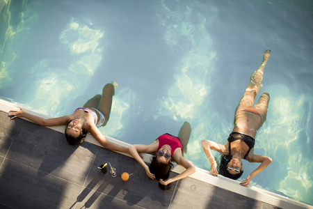 Three beautiful slim young women in bikini relaxing and drink cocktails on poolside of a swimming pool