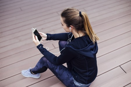 Young sporty woman using cellphone and sittinng on stairs outdoors