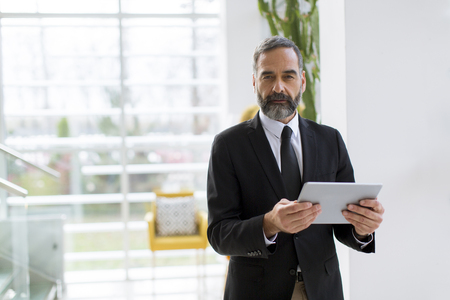 Handsome mature businessman with digital tablet in the office working, reading or searching something