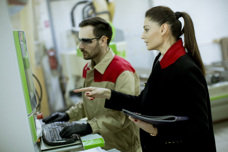 Pretty young woman controlling process in the factory with male worker
