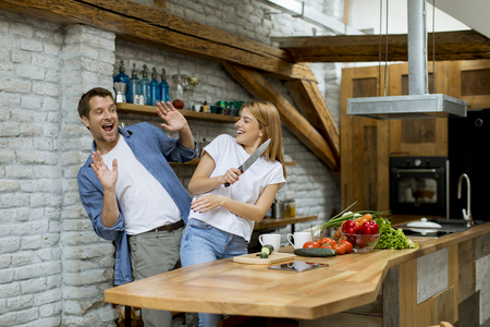 Lovely cheerful young couple cooking dinner together and having fun at rustic kitchen Banque d'images - 123950595