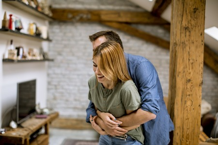 Young man and woman hugging standing at home interior and tender husband embracing wife gently Banque d'images - 123952063