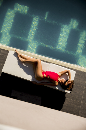 Over view at beautiful tanned woman with sunglasses in red bikini relaxing near luxury swimming pool Banque d'images - 123952065
