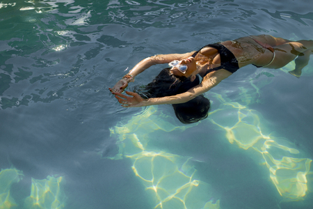 Brunette caucasian woman in  bikini floating in the pool water