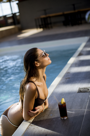 Beautiful slim young woman in bikini and sunglasses relaxing and drink cocktail on poolside of a swimming pool