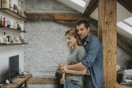 Young man and woman hugging standing at home interior and tender husband embracing wife gently Stock fotó