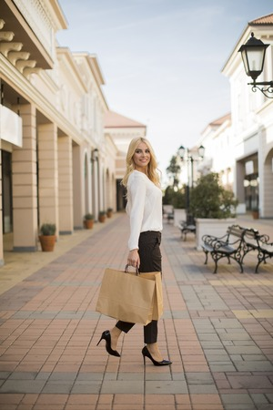 Beautiful woman with paper shopping bag walking by the stores Banque d'images - 123952071