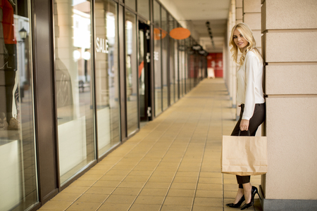 Beautiful woman with paper shopping bag standing by the store Stock fotó