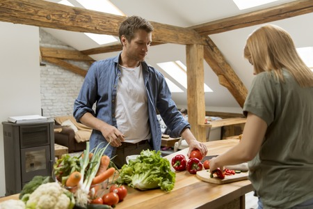 Trendy couple peeling and cutting vegetables from the market in rustic kitchen Banque d'images - 123952078