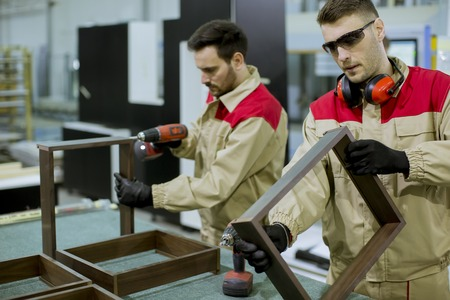 Two handsome young workers assembling furniture in the factory Banque d'images - 123952083