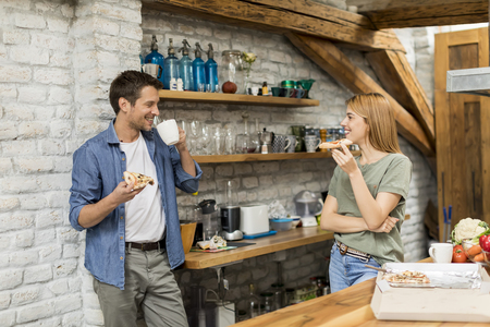 Happy couple eating breakfast together in the rustic kitchen at home Stock Photo