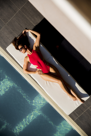 Over view at beautiful tanned woman with sunglasses in red bikini relaxing near luxury swimming pool