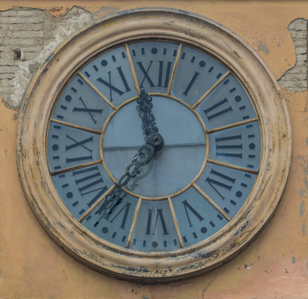 View at old clock on the building in Modena, Italy
