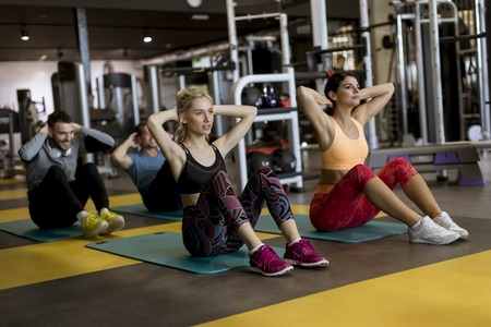 Handsome fit people doing crunches at gym