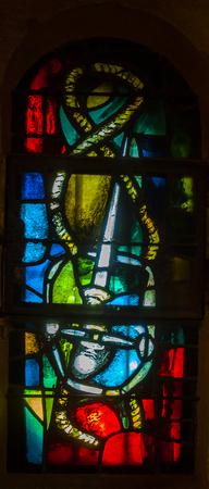 Detail of stained glass from Eglise Saint Vincent des Baux in Les Baux-de-Provence, France Banque d'images - 124399992