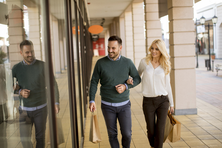 Portrait of young couple with paper shopping bags in city